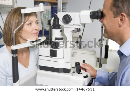 Optometrist in exam room with woman in chair - stock photo