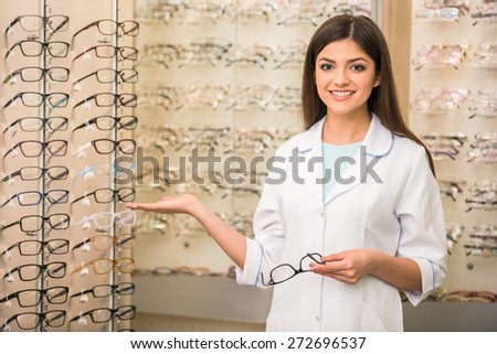 Optometrist is looking at the camera in glasses store. Professional young worker woman. - stock photo