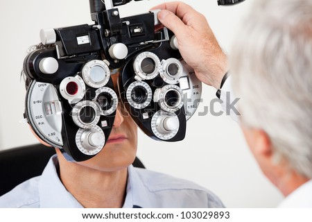 Optometrist performing eye test with phoropter on a male patient - stock photo