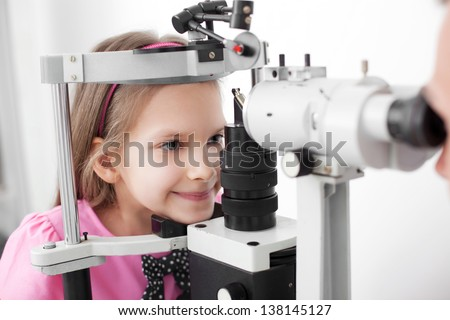 Optometrist performing visual field test of young girl - stock photo