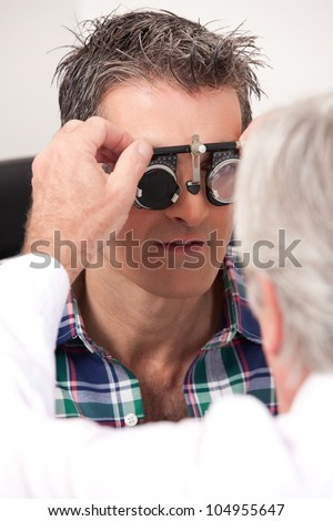 Optometrist using measuring spectacles on patient - stock photo