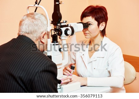 Optometry concept. female optometrist optician doctor examines eyesight of female patient in eye ophthalmological clinic  - stock photo