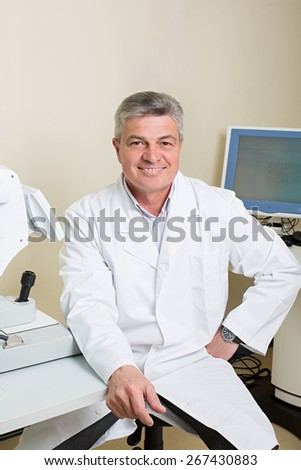 Optometry concept -  portrait of handsome elderly eye doctor - stock photo