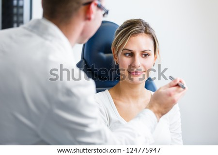 Optometry concept - pretty young woman having her eyes examined by an eye doctor/optometrist (color toned image; shallow DOF) - stock photo