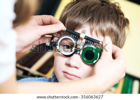 Optometry concept. Young boy with phoropter during sight testing or eye examinations in ophthalmological clinic - stock photo