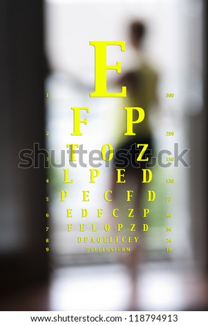 optotype vision chart over a blurred image of a woman - stock photo
