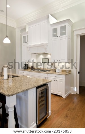 opulent white kitchen with granite countertops and wine fridge - stock photo