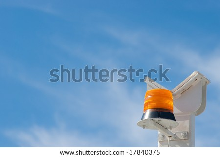 Orange alarm flasher flashlight on white stand against blue sky - stock photo
