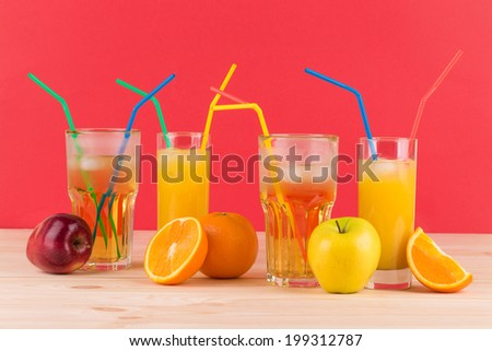 Orange and apple juices on wooden table. On a red background. - stock photo