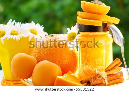 orange and apricot jam in jar on garden table - stock photo