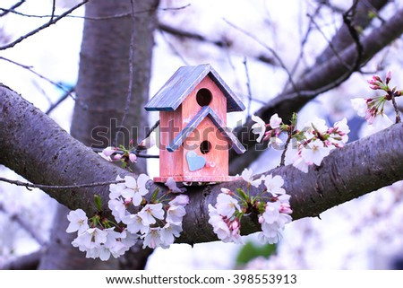 Orange and blue birdhouse with heart hanging from spring flowering tree branch; white blossoms blurred in background - stock photo