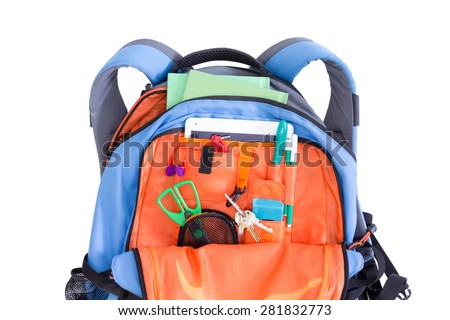 Orange and blue kids school backpack packed with a tablet, notebooks, scissors, pens, books, and stationery ready for a creative art class in an educational concept, on white - stock photo