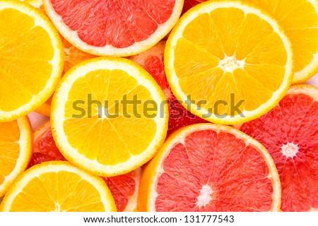 Orange and grapefruit rings as background - stock photo