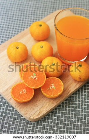 Orange and orange juice on the cutting board - stock photo
