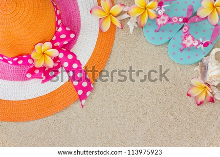 Orange and pink hat and  blue Flip Flops in the sand with shells and frangipani flowers. Summertime on beach concept. - stock photo