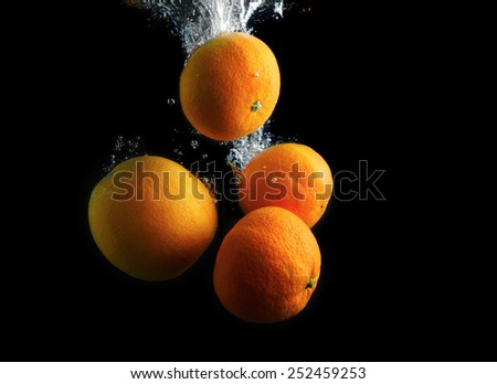 Orange and tangerines in water with air bubbles. Wash fruits. Photo on a black background. - stock photo