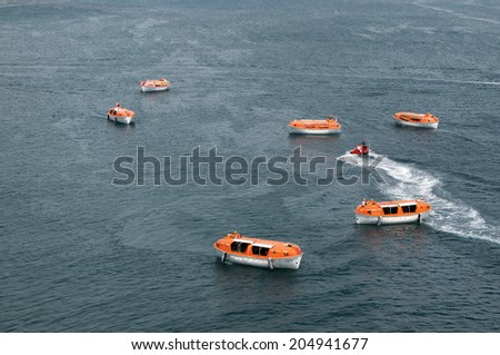 Orange and white lifeboats training and testing for safety requirements - stock photo