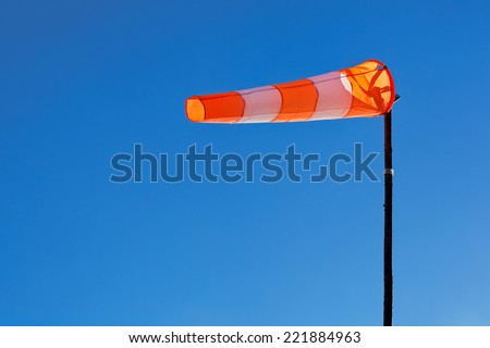 Orange and white windsock blows against a blue sky. - stock photo