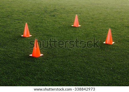 orange and yellow cones in football field - stock photo