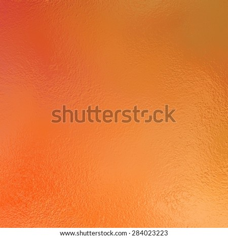 orange background with glossy metallic foil texture. Halloween background color. - stock photo