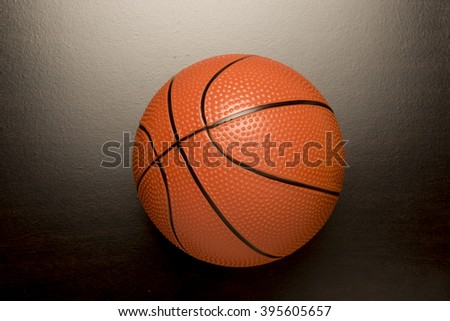 Orange ball  on a dark surface/ Basketball/Sports equipment for competition and recreation. - stock photo