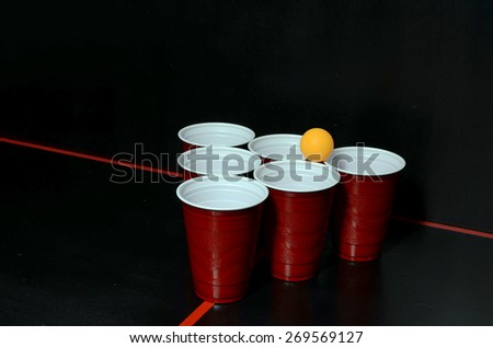 Orange ball on top of beer pong set up - stock photo