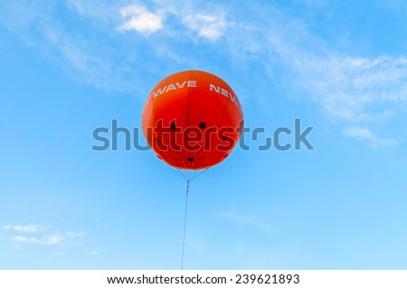 Orange balloon and a cloudy blue sky in the background - stock photo