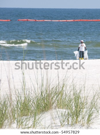 ORANGE BEACH, AL - JUNE 10:  A BP oil spill worker holds an oil debris collection bag amongst sand dunes on June 10, 2010 at Perdido Pass, AL. - stock photo