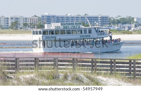 ORANGE BEACH, AL - JUNE 10: A dolphin viewing cruise ship navigates around oil boom as oil approaches on June 10, 2010 in Perdido Pass, AL. - stock photo