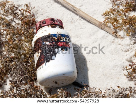 ORANGE BEACH, AL - JUNE 10: A plastic bottle covered with thick black oil washes ashore on June 10, 2010 at Perdido Pass, AL. - stock photo