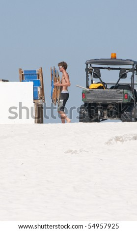 ORANGE BEACH, AL - JUNE 10:  A resort worker puts away lounge chairs early on a beautiful day on June 10, 2010 at Perdido Pass, AL since tourists are away from the beach area. - stock photo