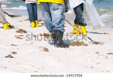 ORANGE BEACH, AL - JUNE 10: BP oil spill workers wearing rubber boots attempt to remove thick globs of oil from the seashore of Perdido Pass, AL on June 10, 2010 as oil washes ashore in the resort area. - stock photo