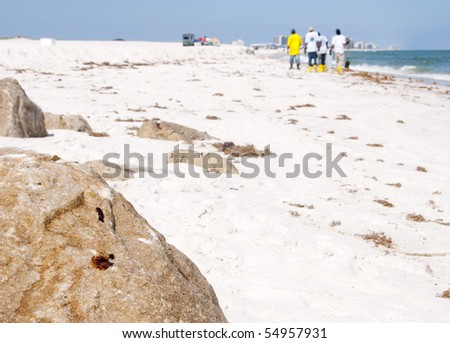 ORANGE BEACH, AL - JUNE 10:  Clean-up workers walk past thick drops of black oil on jetty boulders on June 10, 201 at Perdido Pass, AL. - stock photo