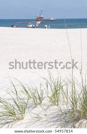 ORANGE BEACH, AL - JUNE 10:  Oil spill workers attempt to clean up oil along the beach in a tourist resort area on June 10, 2010 in Orange Beach, AL. The beaches are empty except for the workers in the height of the tourism season. - stock photo
