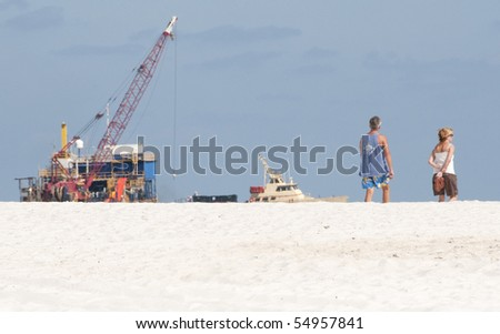 ORANGE BEACH, AL - JUNE 10:  Tourists stroll past huge oil spill machinery in place at Peridido Pass, AL on June 10, 2010 as oil washes ashore. - stock photo