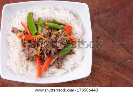 orange beef stir fry over white rice. made with flank steak - stock photo