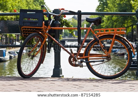 orange bike and the canals of Amsterdam - stock photo