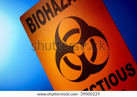 Orange bio hazard sign dramatically shot in front of glowing blue background - stock photo
