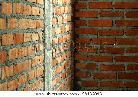 Orange brick wall with cement is formed with reinforced concrete columns to increase their strength. - stock photo