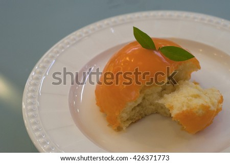 Orange Cake on plate with grass table background with reflect light , close up cake  - stock photo