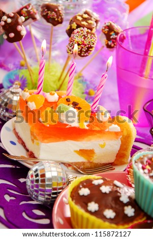 orange cake with three candles on birthday party table for child - stock photo