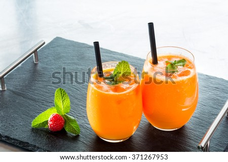 Orange carrot fresh fruit juice smoothie mint glass size small large straw black stone table - stock photo