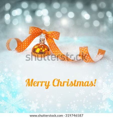 """Orange Christmas bauble on a neutral winter background with a caption """"Merry Christmas!"""" on neutral winter background.  - stock photo"""