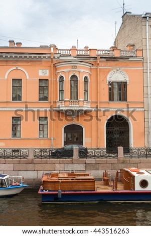Orange classic house with a bay window and an arched gate on the Moika River. - stock photo