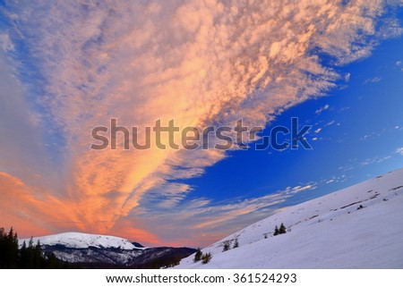 Orange clouds above snow covered mountains in winter - stock photo