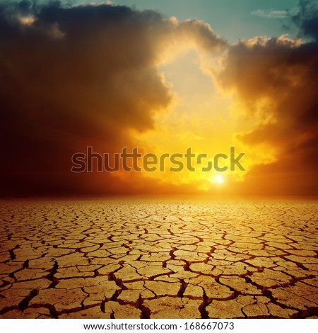 orange cloudy sunset over cracked desert - stock photo