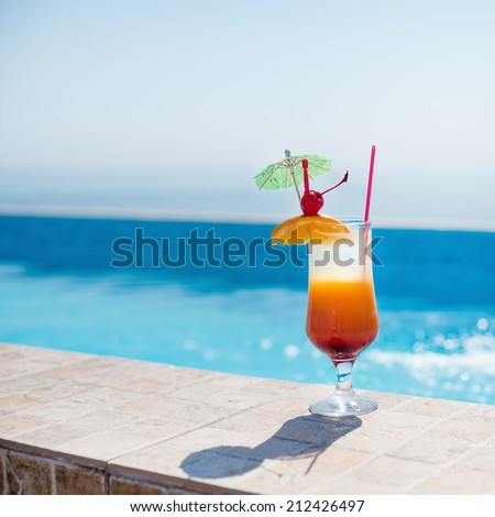 Orange cocktail near the pool at sunny day - stock photo