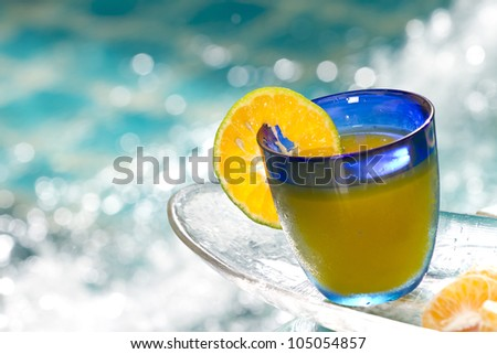 orange cocktail, orange cocktail in blue glass by Jacuzzi pool - stock photo