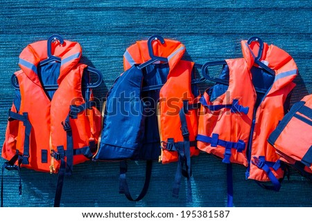 Orange color life jackets, hanging on the wall of the boating station covered with blue guard net - stock photo
