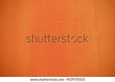 Orange color paint on concrete wall:Close up,select focus with shallow depth of field:Macro shot. - stock photo